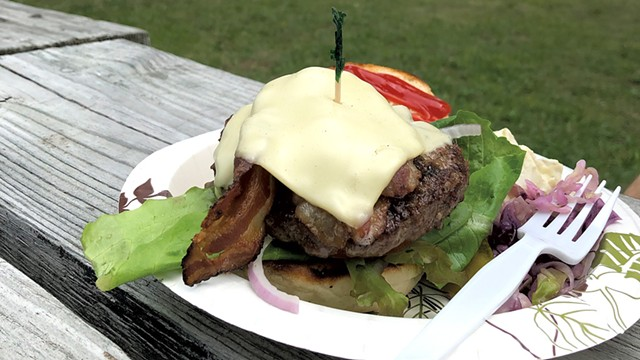 A burger on a picnic table overlooking the lake - STINA BOOTH