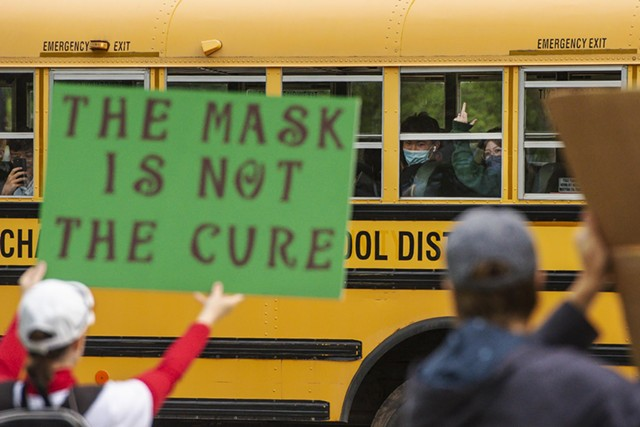 Fiona, from the bus, flips off the protesters - GLENN RUSSELL/VTDIGGER