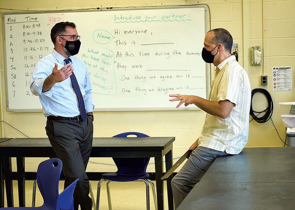 Tom Flanagan (left) talking with science teacher Nathan Caswell during a tour of Hunt Middle School - BEAR CIERI