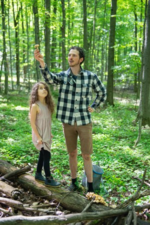 Ari Rockland-Miller showing an example of a nonedible mushroom while his daughter Eliana Rockland-DiMare, 7, looks on at Shelburne Farms - DARIA BISHOP