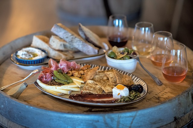 A cheese and charcuterie plate, marinated olives, whipped ricotta with Trent's Bread, and a flight of wine - DARIA BISHOP