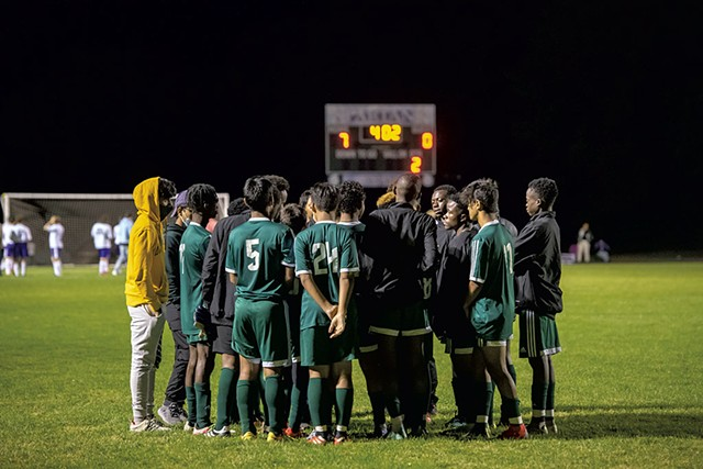 Winooski High School boys' soccer team huddling during a game against Oxbow High School - DARIA BISHOP