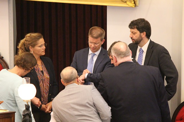 House Speaker Shap Smith (D-Morristown) checks his watch while huddling with House leaders Thursday at the Statehouse. - PAUL HEINTZ