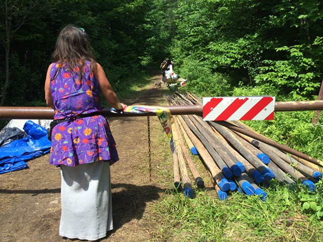 """A woman who goes by """"Feather"""" stands at the campsite entrance by poles that will be used to construct teepees. - MARK DAVIS"""