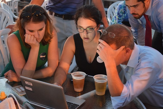 House Speaker Shap Smith (D-Morristown) looks over results early Tuesday evening at Breakwater Café & Grill with campaign manager Erika Wolffing (left) and supporter Candace Morgan. - TERRI HALLENBECK