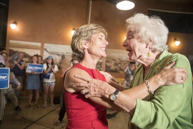 Democratic gubernatorial nominee Sue Minter embraces former governor Madeleine Kunin Tuesday night in Burlington. - JAMES BUCK