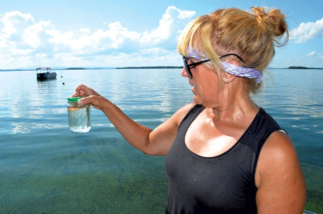 Cathy Hickory with a sample of lake water - MOLLY WALSH