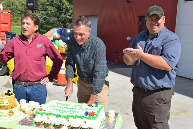 Republican gubernatorial candidate Phil Scott (center) cuts a cake commemorating DuBois Construction's 70th anniversary, with co-owner Don DuBois (left) and new partner Jeff Newton Saturday. - TERRI HALLENBECK