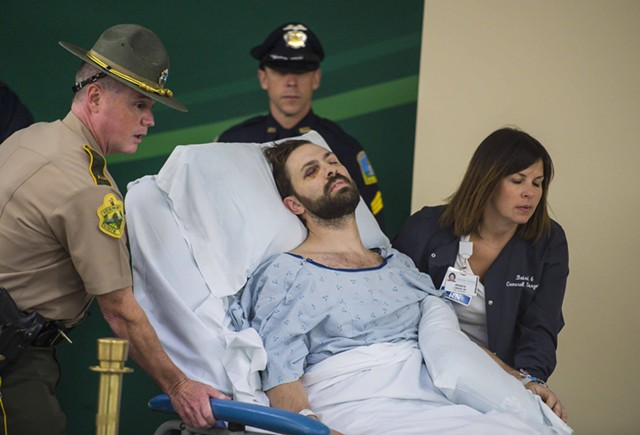 Steven Bourgoin is wheeled into his arraignment at the UVM Medical Center Friday morning. - GLENN RUSSELL/BURLINGTON FREE PRESS