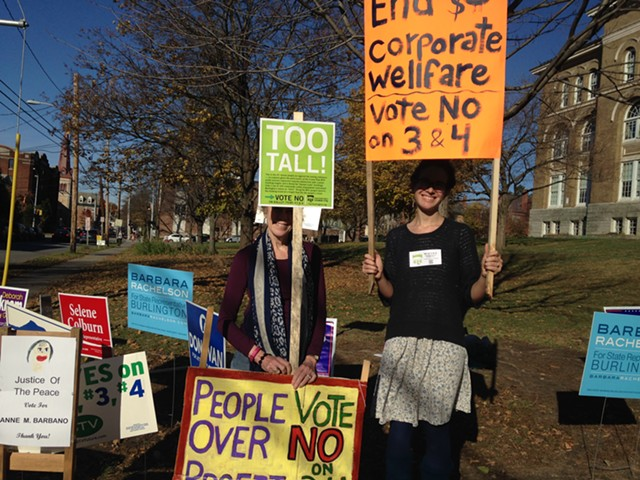 Jennifer Ely (left) and Kylie Dally of Essex hold signs against the Burlington TIF bond and a proposed zoning change to allow for higher buildings downtown. The two were outside the Ward 6 voting place at the Edmunds Middle School in Burlington Tuesday. - MOLLY WALSH