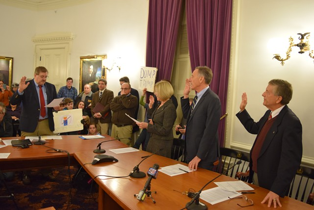 Vermont's electors take the oath Monday in the Statehouse while protesters stand by. - TERRI HALLENBECK