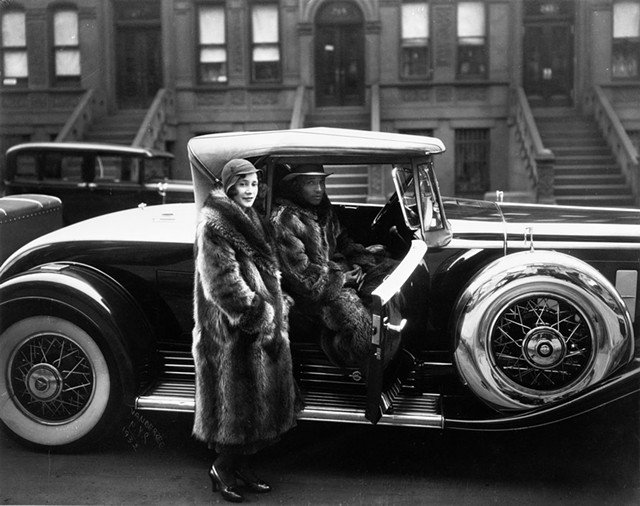 """""""A Harlem Couple Wearing Raccoon Coats Standing Next to a Cadillac on West 127th Street,"""" photograph by James Van Der Zee - COURTESY OF MIDDLEBURY COLLEGE OF ART"""