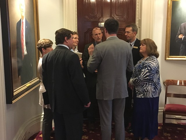 A group of Democratic lawmakers who supported Gov. Phil Scott's proposal confer outside his office Wednesday afternoon. - TERRI HALLENBECK