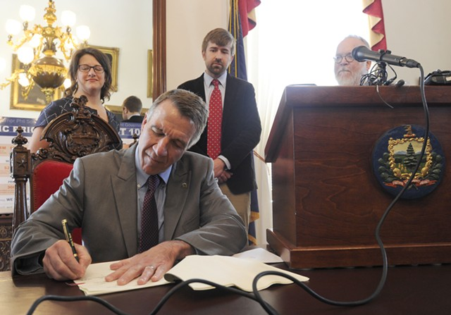 Gov. Phil Scott, surrounded by journalists, signs the shield bill into law. - JEB WALLACE-BRODEUR