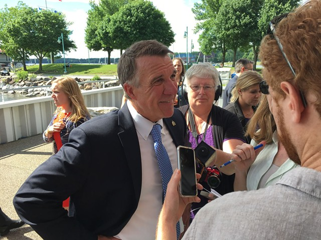 Gov. Phil Scott speaks with reporters after the announcement of the Vermont Climate Pledge Coalition - JOHN WALTERS
