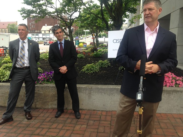 Chris Powell, CEO of Aspenti Health, speaks at Monday's press conference as Burlington Mayor Miro Weinberger (center) and Gov. Phil Scott (left) listen. - MOLLY WALSH/SEVEN DAYS