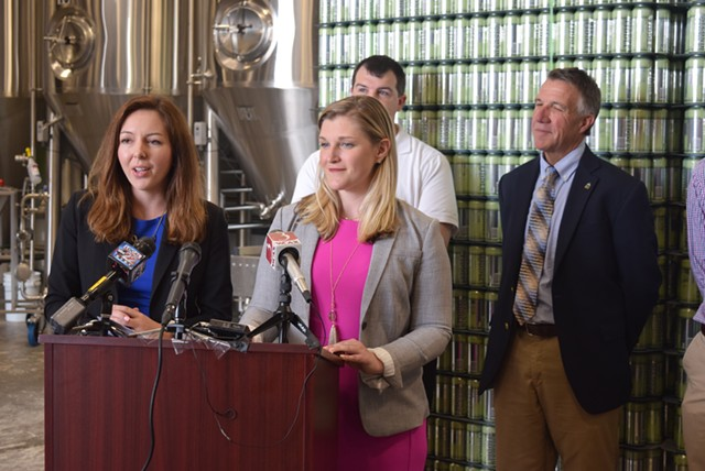 Amanda O'Brien (left) and Laura Pierce talk Monday at Fiddlehead Brewing about helping young adults find work in Vermont as Gov. Phil Scott (right) and Paul Dame  look on. - TERRI HALLENBECK
