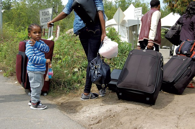 Refugees wait to cross the Canadian border in Champlain, N.Y. - MARK DAVIS