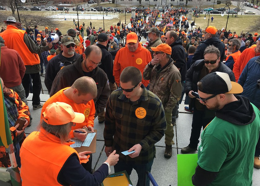 Gun-rights supporters making donations to the Federation of Vermont Sportsmen's Club for a lawsuit against S.55 while others wait in long lines to receive free 30-round magazines. - JOHN WALTERS