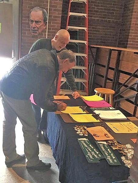 Bert Saldi looking on as Gov. Phil Scott signs a gun-rights letter in February 2017 - COURTESY OF DEVON CRAIG