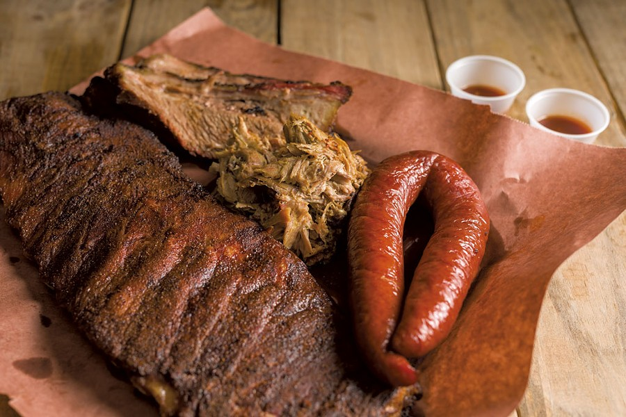 Smorgasbord of smoked meats: ribs, brisket, pulled pork and sausage - OLIVER PARINI