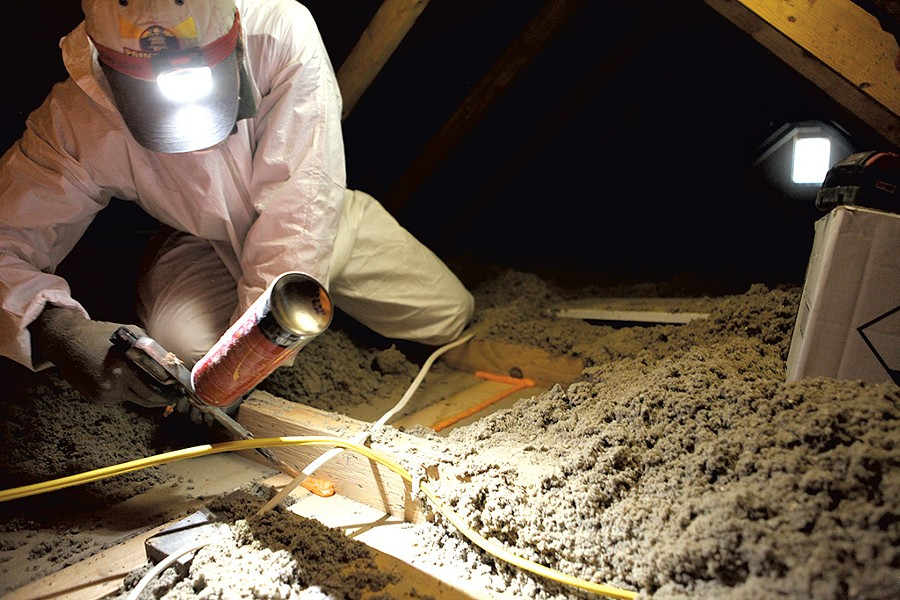 Brian Hyde of Energy Co-op of Vermont, sealing gaps in a Colchester attic - KEVIN MCCALLUM
