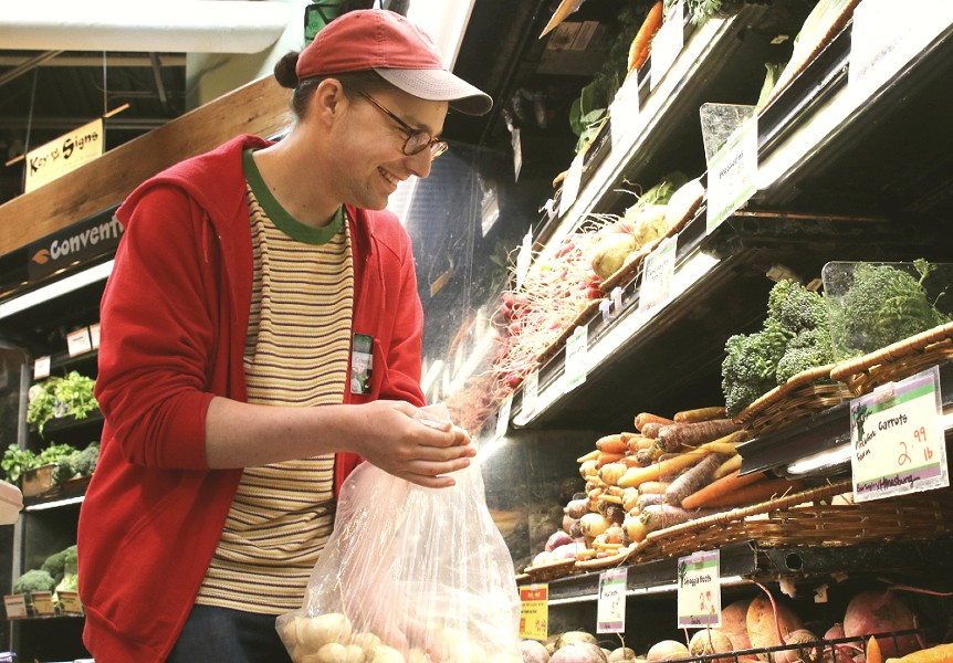 Connor Chilson stocks produce at City Market - COURTNEY LAMDIN