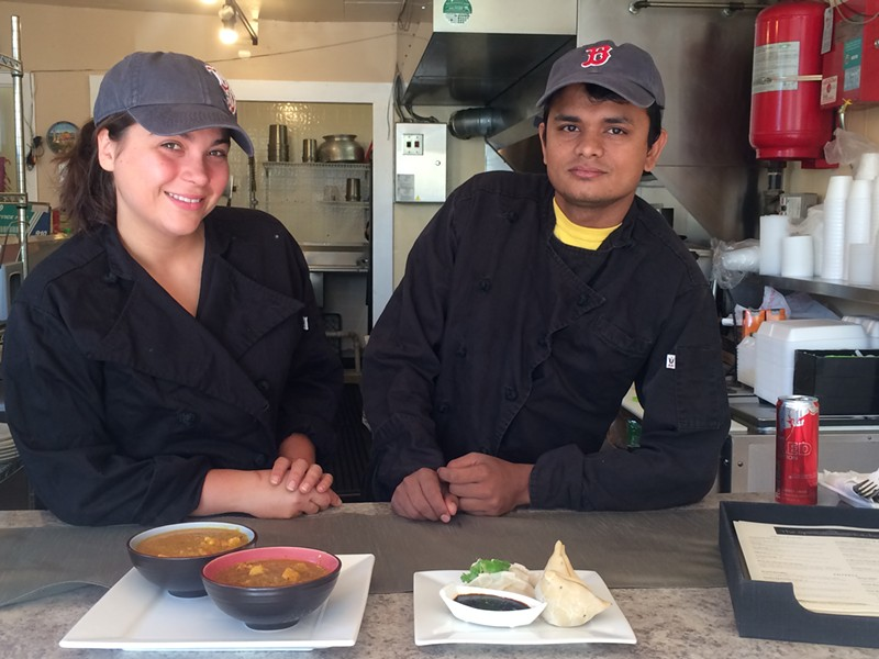 Alyssa Vigneault and Sudershan Adhikari with curries, momos and samosas - ALICE LEVITT