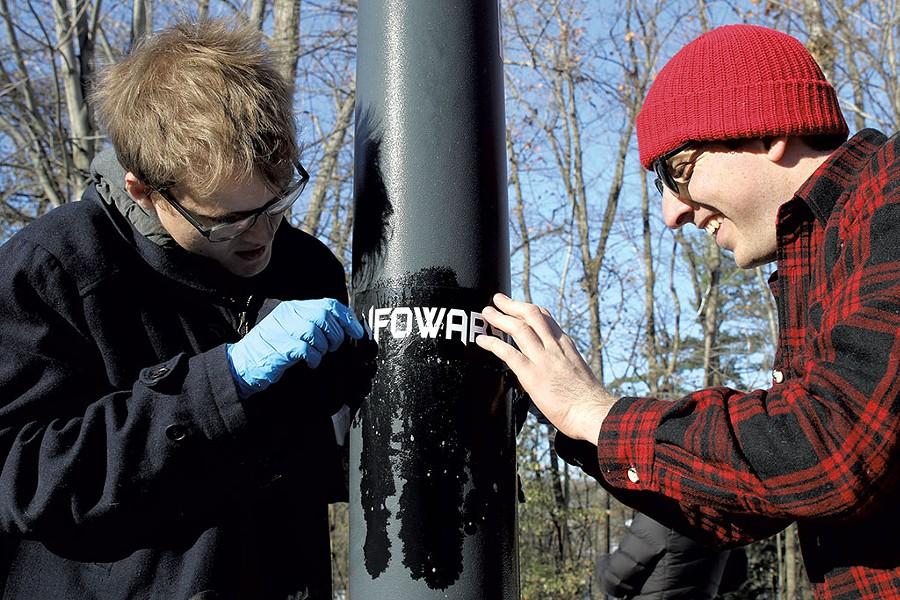 Kason Hudman (left) and Walter Keady trying to remove an Infowars sticker on Riverside Avenue - COURTNEY LAMDIN