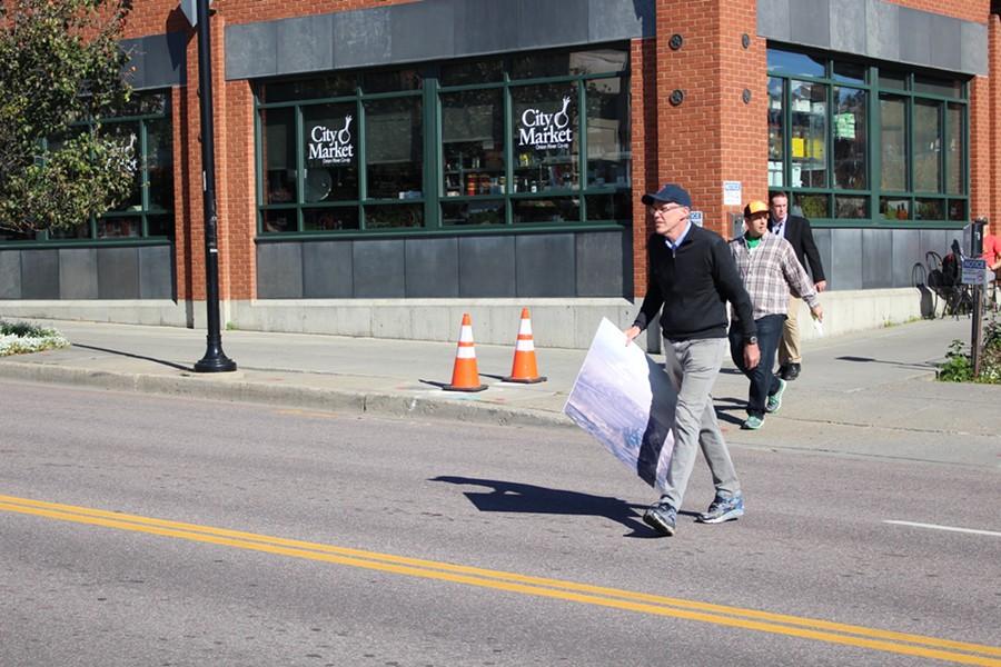 Bill McKibben approaches Handy's Mobil. - PAUL HEINTZ