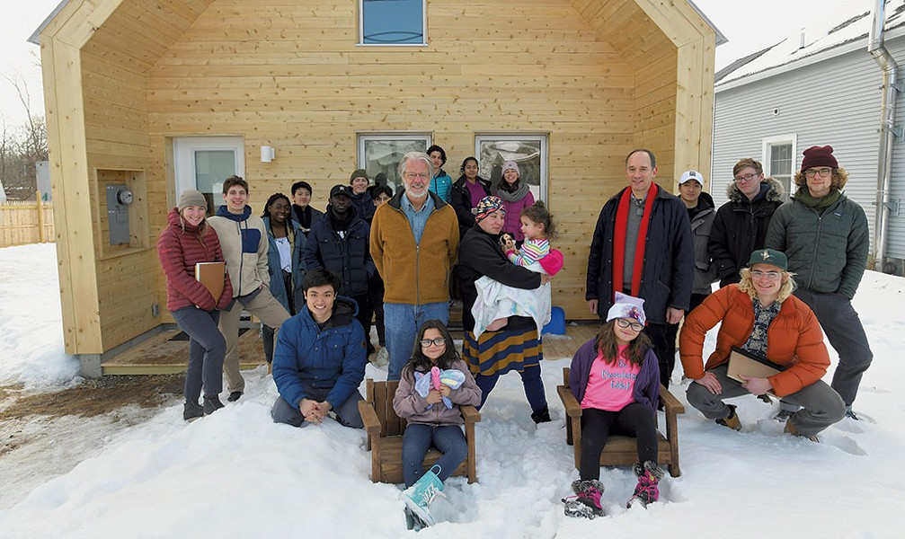 Steve Ingram (center left) and Middlebury College professor John McLeod (center right) with homeowner Dora Rivera (center), her children and McLeod's class - JON OLENDER