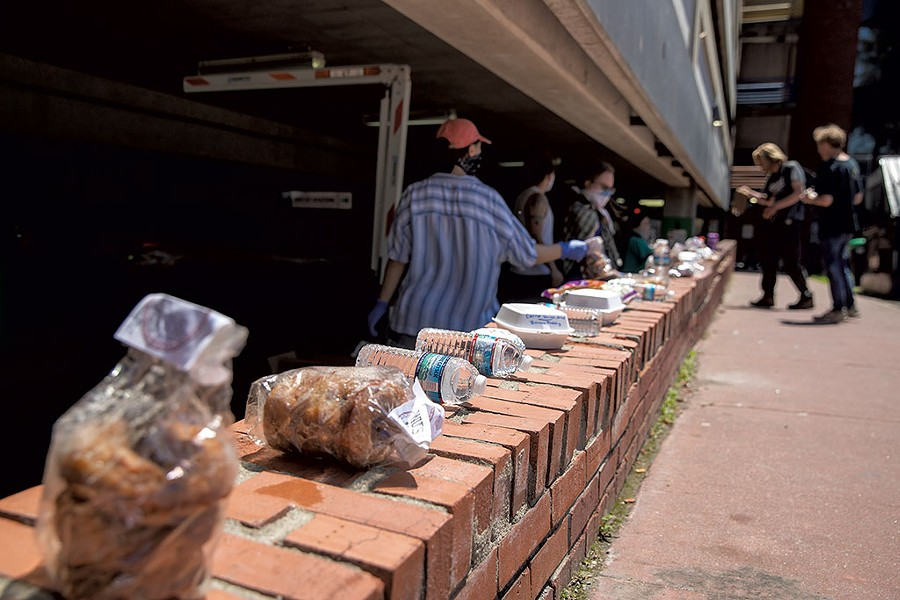 A Food Not Bombs volunteer sorting through donations - JAMES BUCK