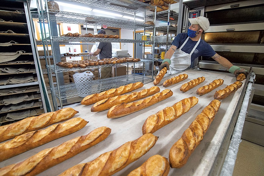 Baker Marc Levy removing fresh-baked baguettes from  the oven - JEB WALLACE-BRODEUR