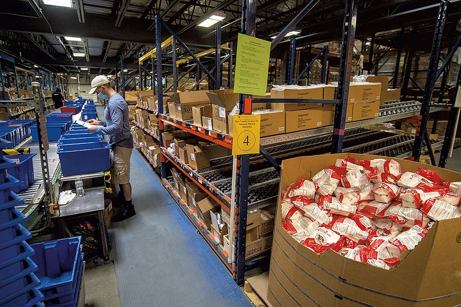 Justin Severance filling mail orders at the fulfillment center - JEB WALLACE-BRODEUR