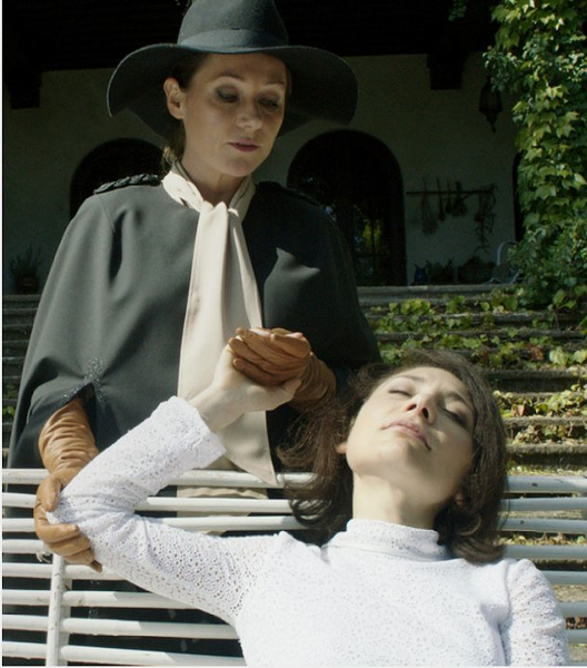 Cynthia (standing) worries about Evelyn's strange rituals and demands. - IFC FILMS