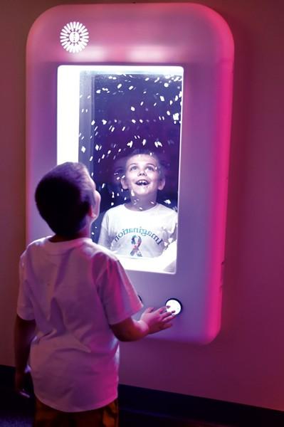 Ethan Slayton, 8, watching virtual snowflakes at an interactive wall panel - JEB WALLACE-BRODEUR