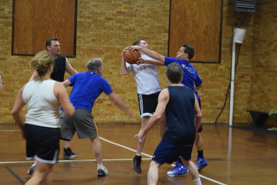 Peter Sterling (in blue) blocks a shot by Matt McMahon (in white) during a legislative and staff basketball game Friday. - TERRI HALLENBECK