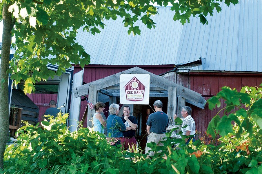 Peter McAlenney (center) talking with patrons at Red Barn Brewing - HANNAH PALMER EGAN