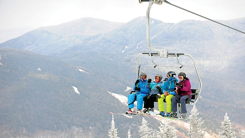 Skiers on a lift at Stowe Mountain Resort, pre-COVID