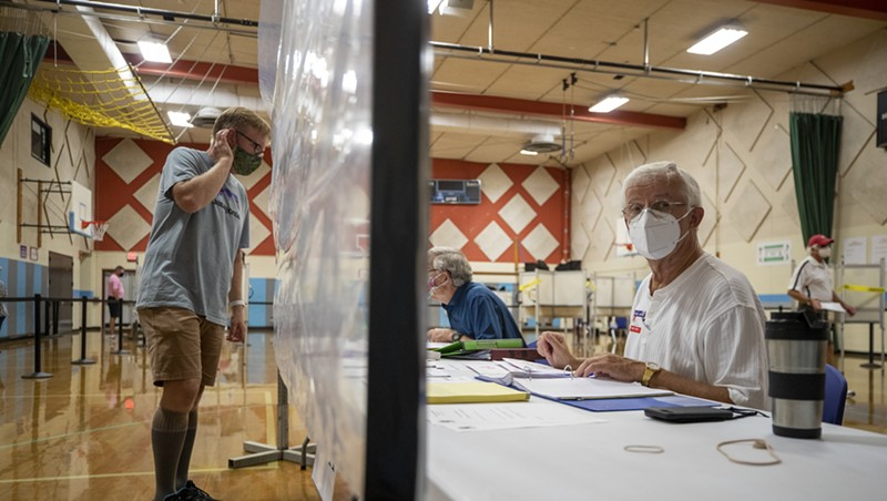 A poll worker behind a sheet of plastic in August