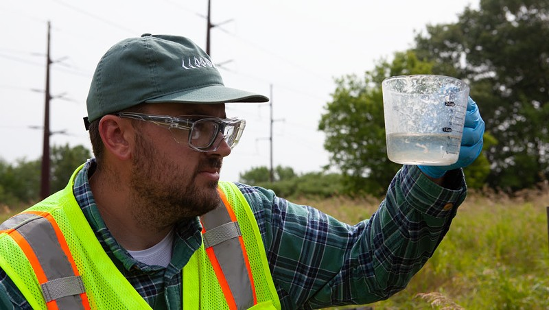 Aaron Sutton, an employee of an environmental firm, testing a well outside the Air National Guard base in South Burlington