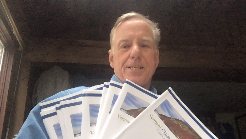 Former governor Howard Dean with multiple information booklets for new claimants that he received