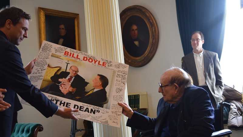 Senate President Pro Tempore Tim Ashe (D/P-Chittenden) presents former senator Bill Doyle with a signed photo Tuesday.
