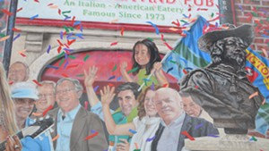 "Miro Weinberger, with his daughter Li Lin sitting astride his shoulders, in the ""Everyone Loves a Parade"" mural"