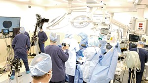 A film crew shooting Dr. Bryan Huber in surgery
