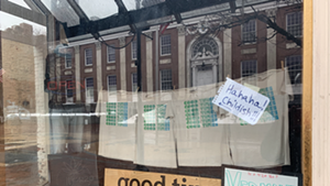 Burlington City Hall is reflected in Good Times Gallery's window.