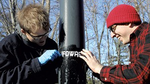 Kason Hudman (left) and Walter Keady trying to remove an Infowars sticker on Riverside Avenue