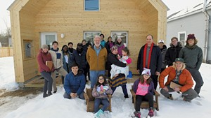 Steve Ingram (center left) and Middlebury College professor John McLeod (center right) with homeowner Dora Rivera (center), her children and McLeod's class