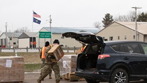 A member of the Vermont National Guard loading a case of MREs into a car in Swanton on April 22