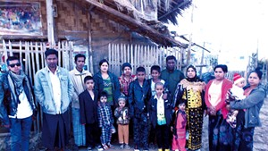 Me Me (in yellow and black) and her family in a refugee camp in Thailand in 2014
